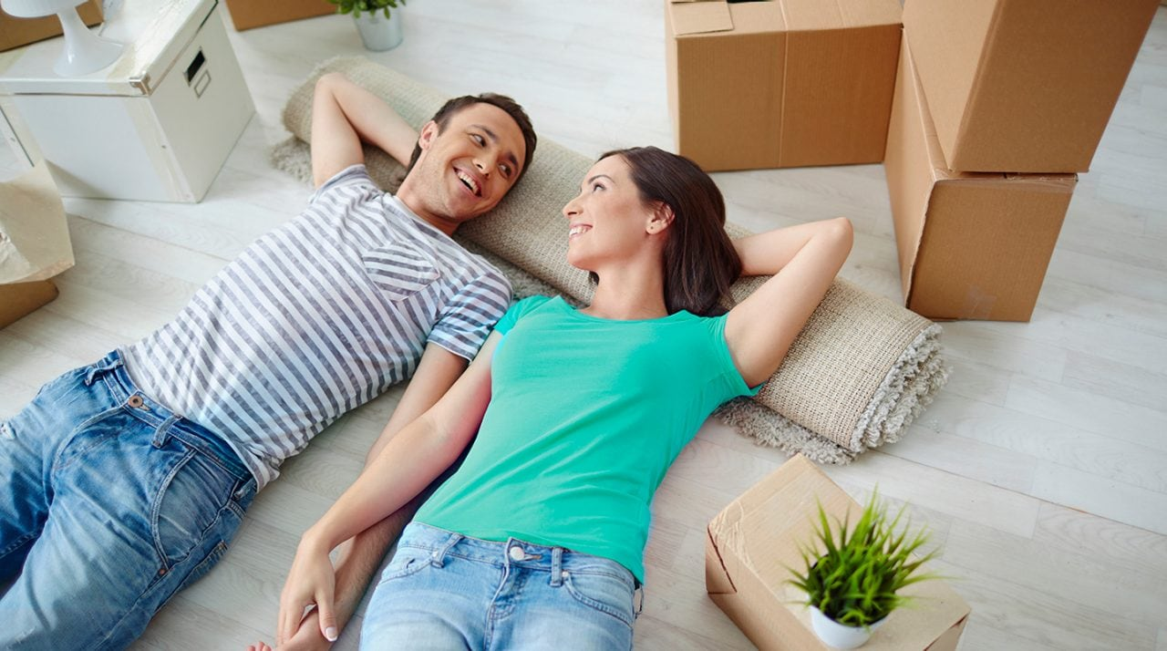 Young man and woman lying on the floor of new house and looking at one another