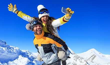 Cheerful young couple hikers making winter selfie on top of the mountain. Both wears warm clothes and gloves, knit hats and sunglasses. Woman in piggyback ride holding the smart phone. Mountain peak and clear sky on background.