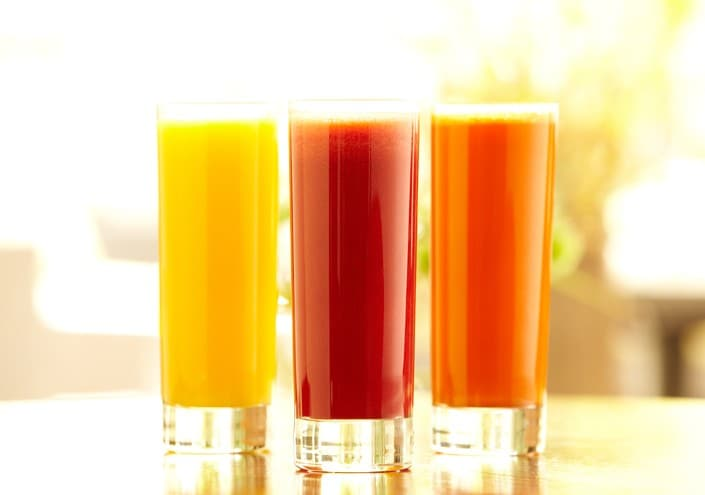 Bright still life shot of three types of juice: orange, carrot and vegetable in tall glasses sitting on a bar counter in a restaurant.  Horizontal shot.