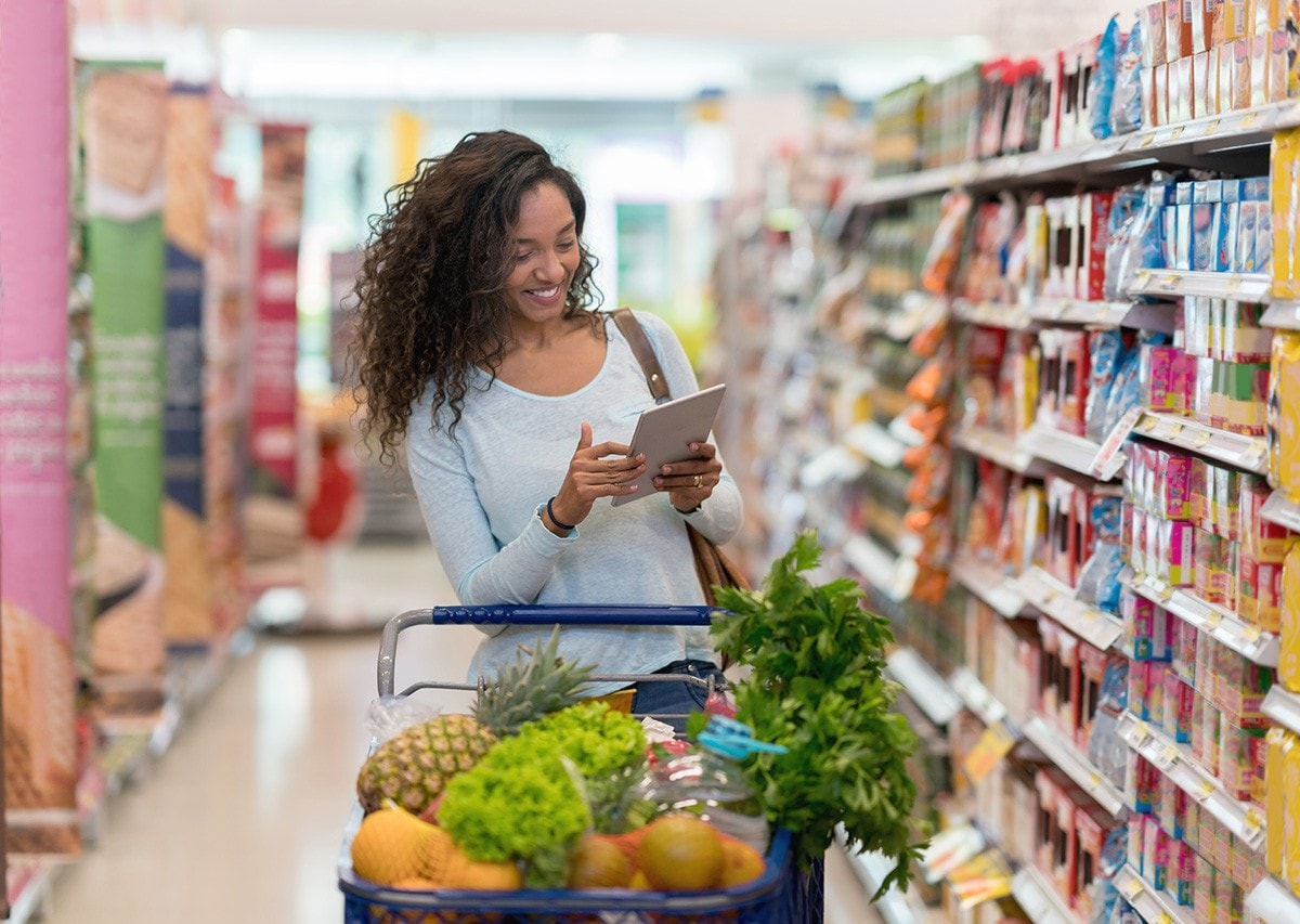 African american woman shopping at the supermarket and looking at the shopping list on a digital tablet looking very happy and smiling
