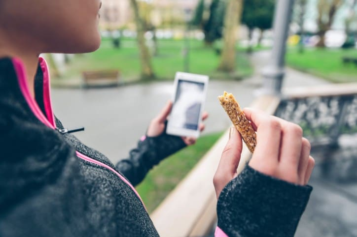 Woman eating cereal bar after training and holding smart phone
