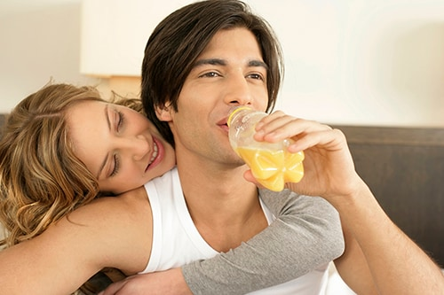 Young man drinking bottled juice, woman embracing him from behind