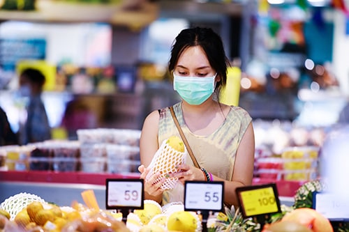 asian woman in medical face mask chooses fruits while shopping in supermarket. covid-19 spreading outbreak