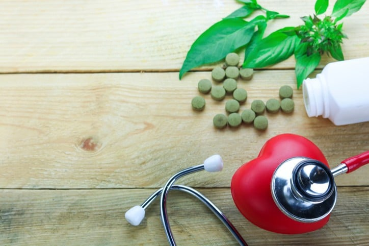 Healthy hearth concept, Herbal Medicines with herb leaf and ear doctor on wood background