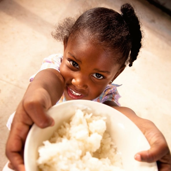 Adorable preschool age African American girl smiles while holding a bowl filled with white rice.