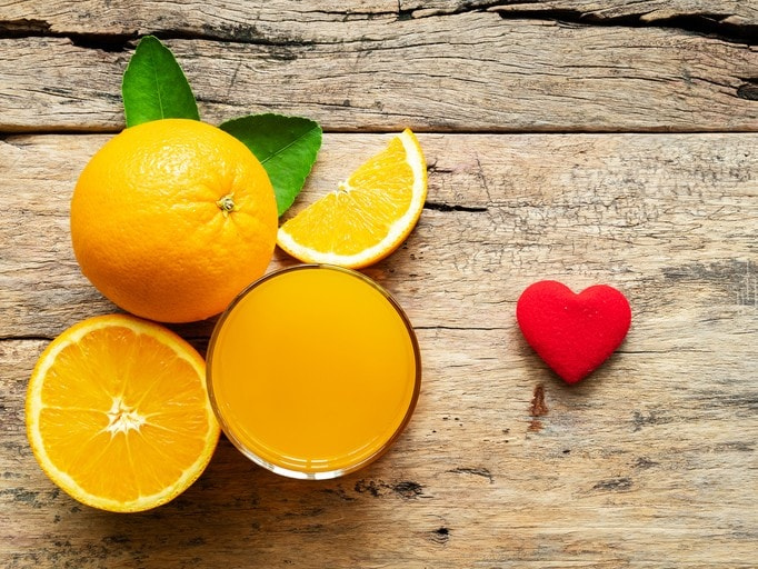 a glass of fresh orange juice and group of fresh orange fruits with green leaves, on wooden background with red heart shape. vitamin C and fruit product display or montage, studio shot
