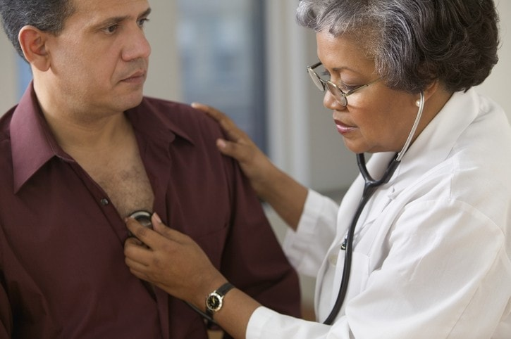 Mature female doctor listening to heart of male patient