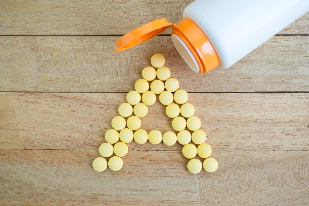 Yellow pills forming shape to A alphabet on wood background