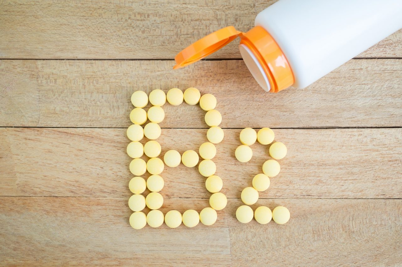 Yellow pills forming shape to B2 alphabet on wood background