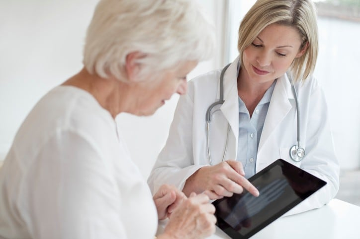 MODEL RELEASED. Female doctor showing senior patient xray of hand on digital tablet.