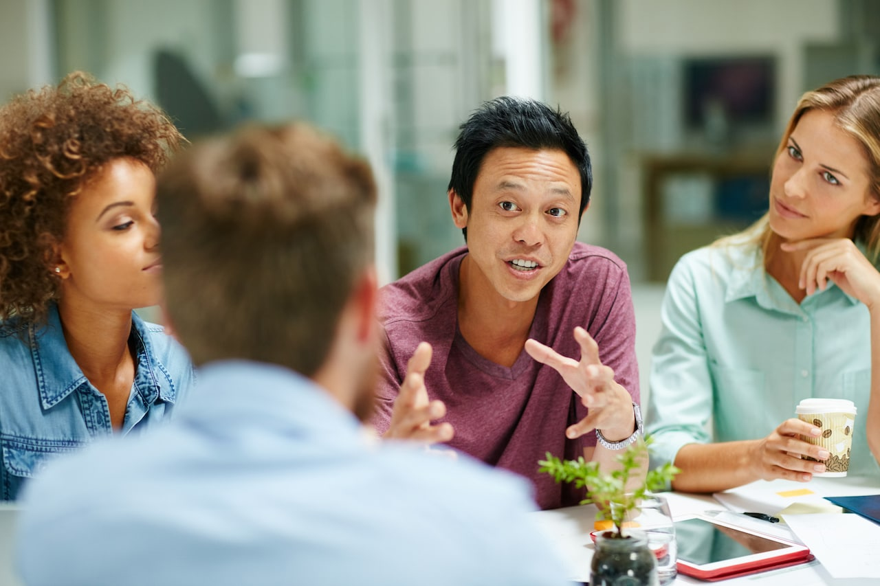Shot of a group of businesspeople talking together around a table in an office