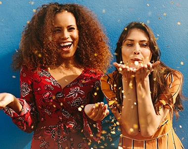 Attractive young women blowing glitters against blue background. Mixed race female friends having fun with glitters.