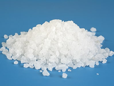 A heap of sea salt with shallow depth of field.